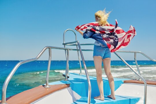 Young blonde woman in denim with flag of America on shoulders, back view, in sea