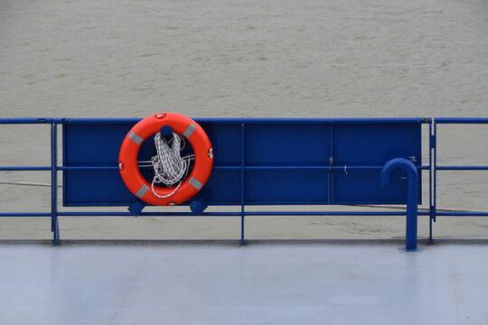 Closeup of an orange lifebelt on the board