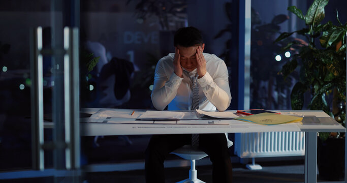 Japanese handsome sad adult businessman losing job having financial problems thinking over life frustrating inside office department. Overworking concept.