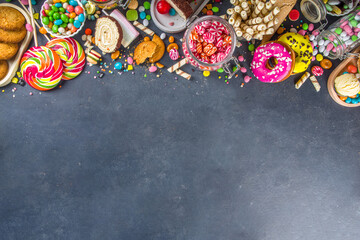 Selection of colorful sweets. Set of various candies, chocolates, donuts, cookies, lollipops, ice cream top view on black concrete background