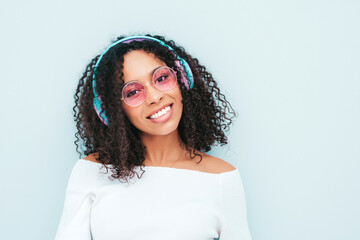 Fototapeta Beautiful black woman with afro curls hairstyle.Smiling model in sweater and jeans.Sexy carefree female listening music in wireless headphones.Posing in studio near light blue wall