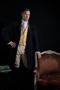 A handsome Regency gentleman standing beside a red velvet chair in a darkened room