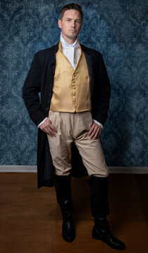 A handsome Regency gentleman wearing a gold waistcoat, breeches, and a black long jacket and standing in a room with blue wallpaper and a wooden floor