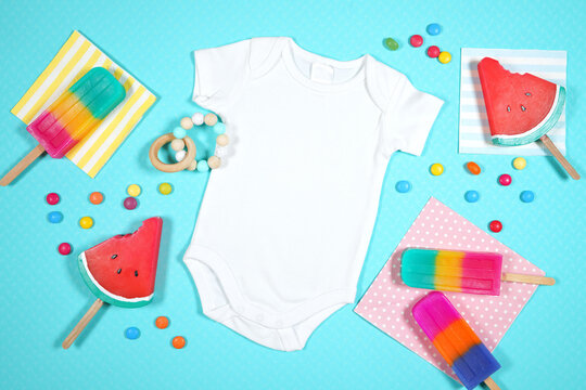 Summer beach vacation theme baby romper bodysuit flatlay styled with watermelon and ice creams on a blue background. White product mock up with negative copy space for your text or design here.
