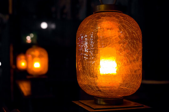 orange oval backyard terrace illumination lantern glows with orange light through cracked glass plafond art design night scene.