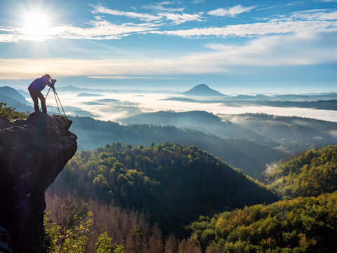 Photographer on mountain witch through viewfinder. Nature photographer taking photo of beautiful morning landscape from top of the mountain