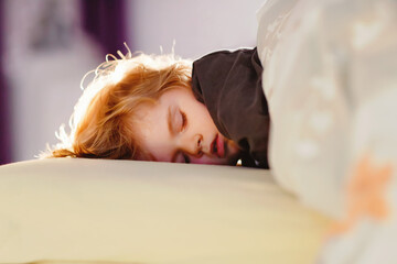 Fototapeta Little toddler child resting on say in parents bed. Adorable kid boy sleeping and dreaming. Peaceful and relaxed rest for children.