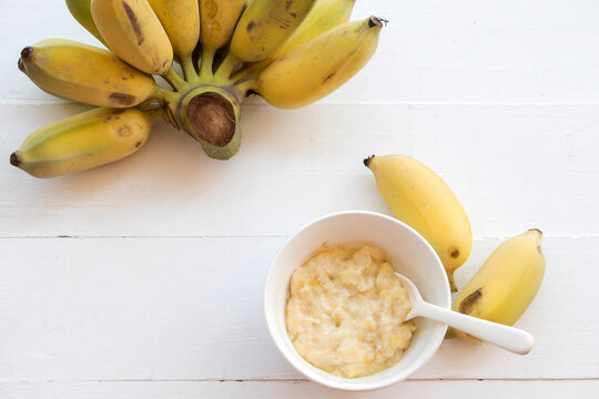 mashed banana healthy foods for baby arrangement flat lay style on background wooden white