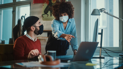 Manager and Programmer Wearing Face Masks, Talk, Solve Problems, Use Computer in Creative Office. App Development Team work on Mobile Game Software, Designer, Developers, Marketing Specialists