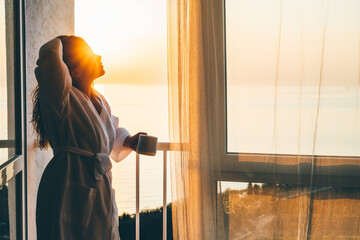 Fototapeta Long haired lady in white bathrobe drinks delicious coffee looking at picturesque sea bay from terrace in hotel room in early morning.