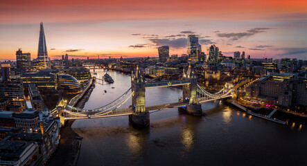 Fototapeta Panoramic, aerial view to the cityscape of London with Tower Bridge and the illuminated skyscrapers of the city during dusk, United Kingdom