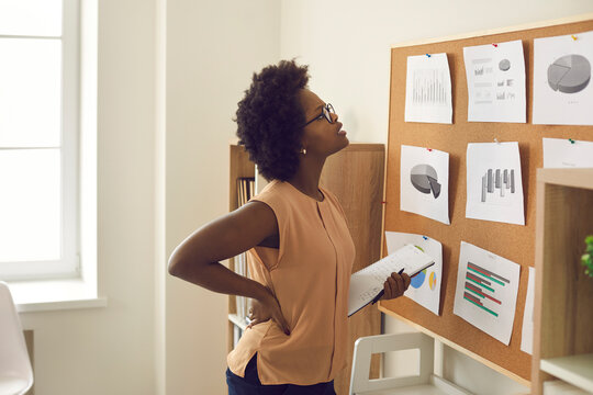 Young african american woman employee brainstorming standing near board with project result looking at paper graphs and charts. Getting new ideas, possibility effort and strategy planning
