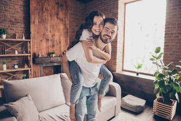 Fototapeta Portrait of attractive careful funny cheerful couple having fun piggy backing spending holiday at loft style interior home house indoor
