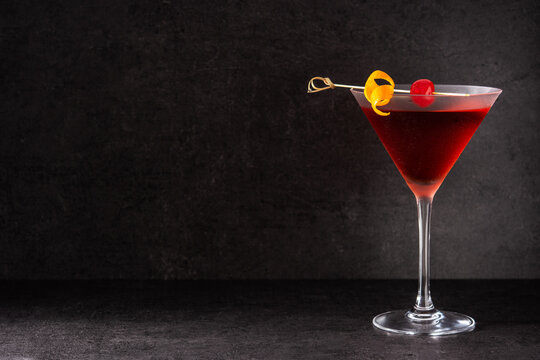 Traditional Manhattan cocktail with cherry on black background.Copy space