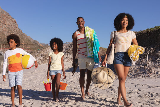 African american parents and two children holding beach accessories walking at the beach