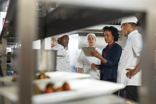 Diverse group of professinal chefs having meeting with kitchen manager