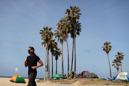 A man runs past homeless encampments lining the bike path, as the coronavirus disease (COVID-19) disease pandemic continues, on Venice Beach in Los Angeles