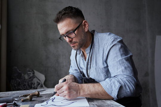 Bearded attractive brunette man in apron and eyeglasses making linocut sketch using felt pen. Lithograph professional artist handmade worker. High quality photo