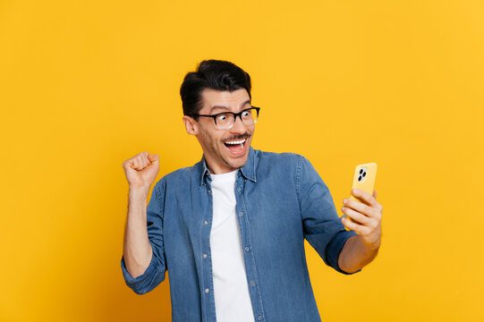 Amazed joyful excited stylish caucasian guy holds smartphone, get unexpected news, winning, stands on isolated orange background, cheerful facial expression, toothy smile, gesturing with fist