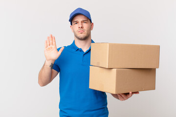 package deliver man looking serious, stern, displeased and angry showing open palm making stop...