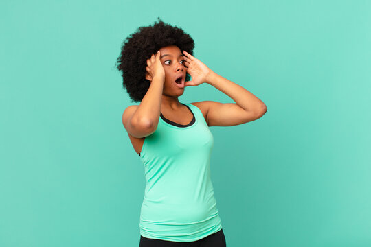 black afro woman with open mouth, looking horrified and shocked because of a terrible mistake, raising hands to head