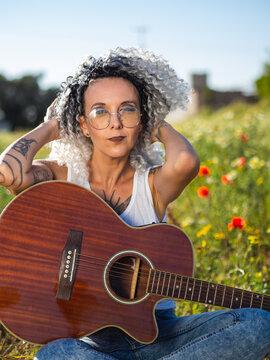 Mujer joven con tatuajes posando con una guitarra en el campo