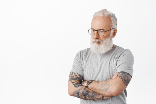 Thoughtful upset senior man in glasses, tattoos on hands, cross arms and look aside with troubled pensive face, thinking, standing over white background