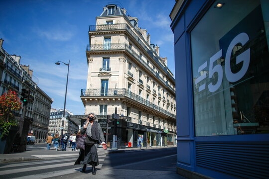 A woman walks past a 5G data network sign at a mobile phone store in Paris