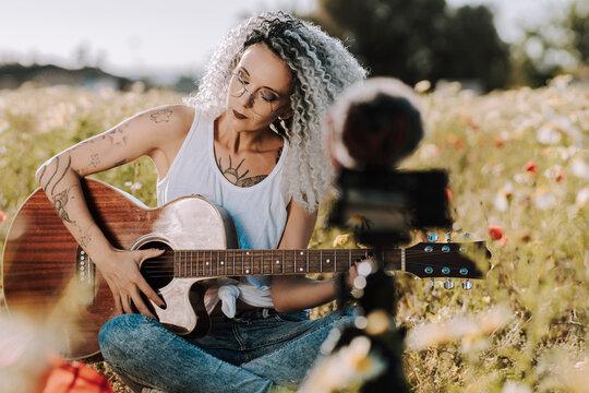 Chica guapa delgada con el pelo muy rizado tocando la guitarra en un campo de margaritas mientras se graba un vlog