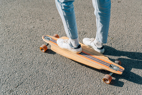 close-up take of the feet of an unrecognizable man on a skateboard on the street asphalt. He is projecting a hard shadow on the asphalt.