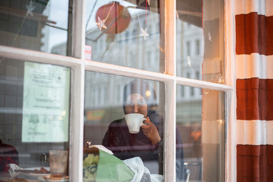 Black Muslim Woman in cafe sipping