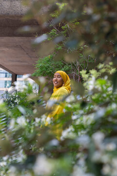 Black Muslim Woman in a yellow scarf in nature