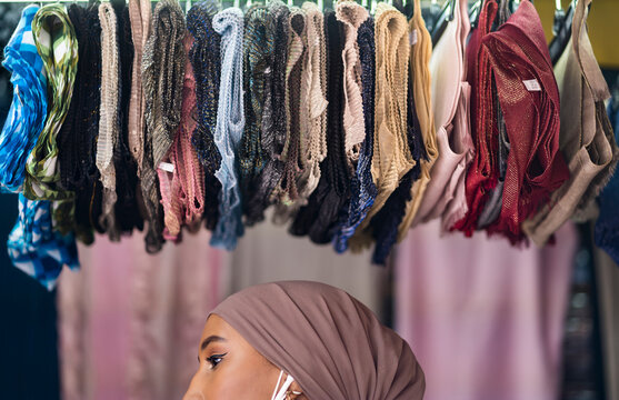 Woman standing under a display of hijabs