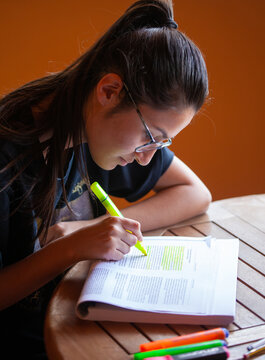 University student studying for an exam underlining text with highlighter.