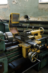 Fototapeta Front view of an old metal lathe in a lathe shop. The lathe components and the spindle.