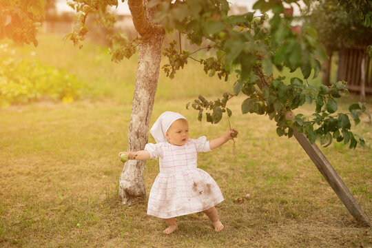 A little girl learns to walk unsteadily while standing under an apple tree. A dirty barefoot child in the village.