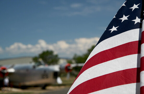 American flag waving to the wind with old airplane in the background