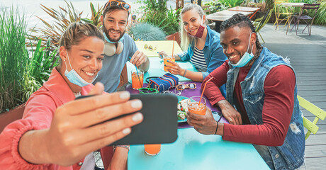 Fototapeta Friends taking selfie in a bar restaurant with face mask on in coronavirus time - Young people having fun with drinks and snacks outside with new rules after virus break