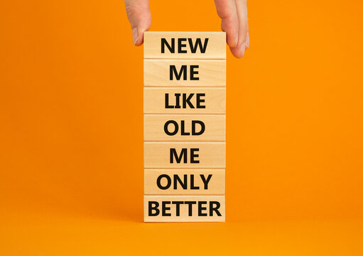 Concept of building success foundation. Men hand put wooden blocks on the stack of wooden blocks. Words 'new me like old me only better'. Beautiful orange background, copy space. New me symbol.
