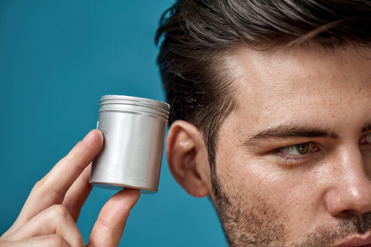 Cropped portrait of brunette guy with bristle looking away, holding silver jar with gel or cream hair styling product isolated over blue background