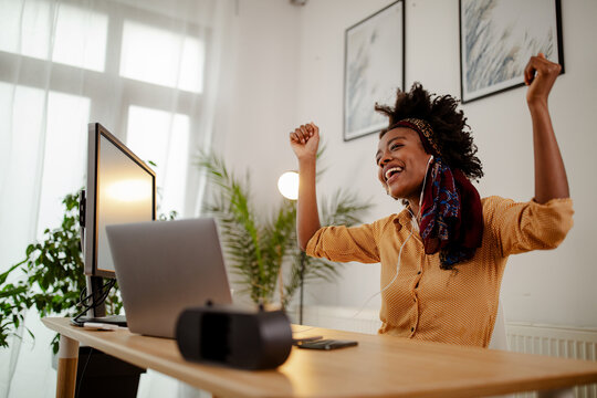 Image of nice woman wearing casual clothes using headphones and dancing while sitting in office.