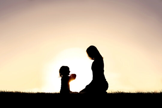 Young Mother and her Little Child are Talking Outside at Sunset