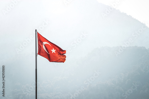 Turkish flag on the background of mountains.  The national flag of Turkey on the background of a mountain. The flag of Turkey on a sunny day develops against the background of the mountains.
