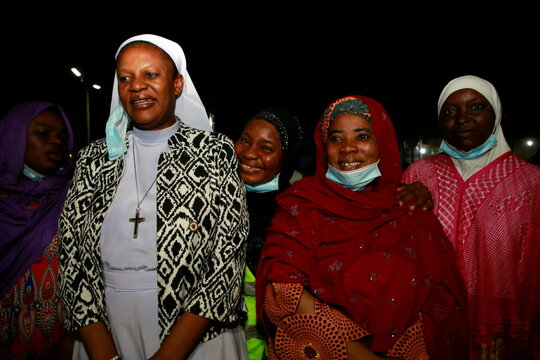 A nun from the Cardinal Onaiyekan Foundation for Peace stands with Muslim women after Muslims break their fast at Al-Habbiyah Mosque in the Guzape District of Abuja