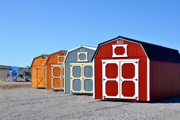 Fototapeta Colorful wooden sheds on display. American shed is typically a simple, single-story roofed structure in a back garden or on an allotment that is used for storage, hobbies, or as a workshop. obraz