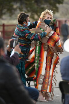 Navajo Nation Council Member Eugenia Charles Newton helps U.S. first lady Jill Biden cover up with a blanket, during a live radio address with Navajo Nation President Jonathan Nez and his wife Phefelia Nez in Window Rock