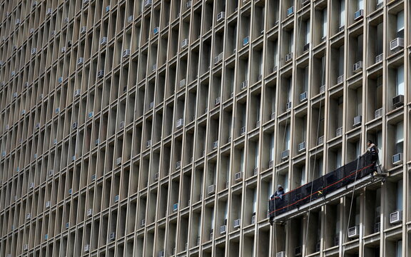 Window washers work on a building featuring rows of window air conditioners in Manhattan