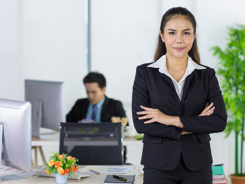 Portrait asian adult woman is office people wearing suit standing and folded cross his arms looking at camera look to confident. Backward are man employee sitting at work desk with blurry background