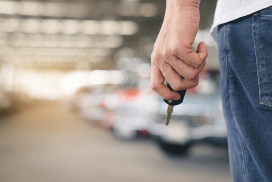 Auto business, car sale or rent concept. Hands of salesman with folder holds a car key over auto show background,copy space for text.