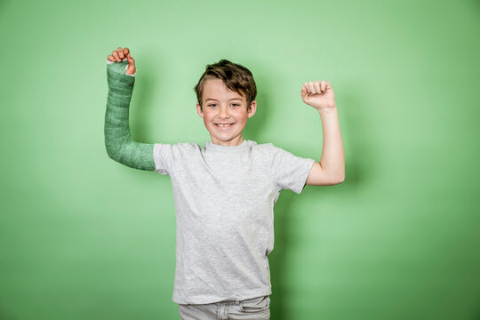 cool young schoolboy with broken arm and green arm plaster posing in front of green background